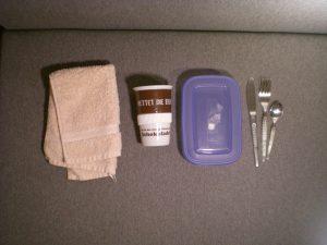 kleines Handtuch, Keramik-Kaffeebecher, Plastikdose, Messer, Gabel, Löffel