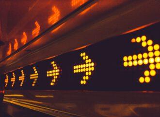 Titelbild, welches leuchtende in eine Richtung zeigende Pfeile an einer Gangwand zeigen.